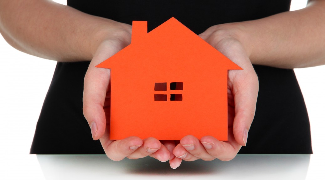 Paper house in hands isolated on white